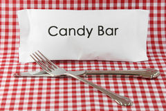 A candy bar meal. A knife and fork and a candy bar meal metaphor on a red gingham background stock photo