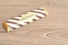 A candy bar with a wrapper. On a wooden background Royalty Free Stock Photo