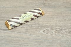 A candy bar with a wrapper. On a wooden background Stock Photos