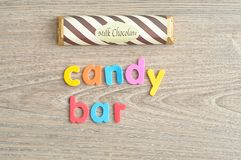 A candy bar with a wrapper with the word candy bar. A candy bar with a wrapper  on a wooden background with the word candy bar Royalty Free Stock Photo