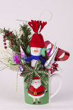 Candy baskets gift in the green cup for new year decoration. Vertical image with  holiday decorated cup. In the center of the image is a little toy -snowman in Royalty Free Stock Photo