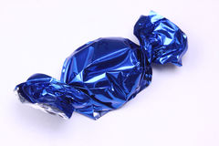 Sweet in blue foil wrapping Royalty Free Stock Images
