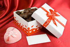 Candy box and prsent. Box with chocolate and present on the red background Stock Photography