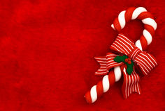 Candy Cane. A candy cane with a bow on a red textured background, Candy cane royalty free stock photo