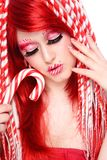 Candy cane. Beautiful young freaky girl with fancy make-up and hairdo Royalty Free Stock Photo