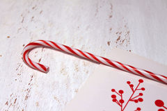 Candy cane and Christmas card. On a wooden surface Royalty Free Stock Photography