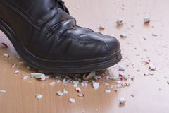 Candy cane crush. Closeup man's black dress shoe stepping onto and shattering Christimas candy cane on wood floor Royalty Free Stock Image