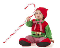 Candy Cane Elf. An adorable toddler holding a giant candy cane as he's dressed like an Christmas Elf. Isolated on white royalty free stock images