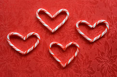 Candy cane hearts. Red and white miniature candy canes in heart shape on red poinsettia background Royalty Free Stock Photo