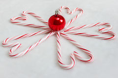 Candy Cane Hearts and Red Christmas Ornament. Candy canes assembled to create heart shapes with shiny red glass blown ornament in center.  White snowy background Royalty Free Stock Image