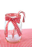 Candy cane in mason jar. Christmas candy cane in mason jar with red and white gingham bow royalty free stock photography