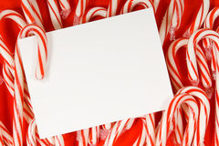 Candy cane notecard. Several candy canes on red background with a blank white notecard in the center with copy space Royalty Free Stock Image