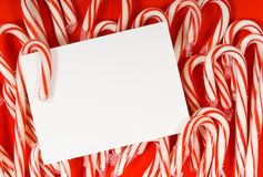Candy cane notecard. Several candy canes on red background with a blank white notecard in the center with copy space Stock Images