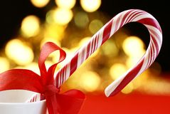 Candy cane. With red ribbon on holiday lights background royalty free stock image
