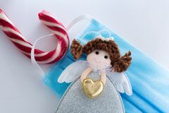 Free Candy Cane With Hookedand Blue Protective Medical Face Mask For Covid-19 And Angel Figurine. Christmas Decoration On White Royalty Free Stock Photo - 203393525