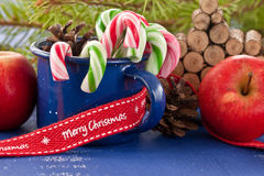 Candy canes in blue cup Royalty Free Stock Photos