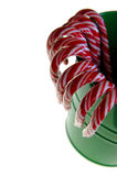 Candy canes in bucket. Red and white christmas candy canes in a green bucket on a white background stock photography