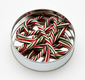 Candy canes in can. Several candy canes shot in decorative tin gift can on white background with soft shadow Stock Image