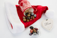 Candy canes, candies and chocolate on Santa hat isolated Royalty Free Stock Photos
