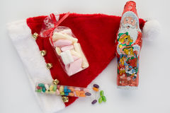 Candy canes, candies and chocolate on Santa hat isolated Royalty Free Stock Photo