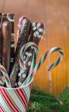Candy canes and chocolate pretzels close up. Candy canes and chocolate pretzels  in a candy cane stripped mug close up Royalty Free Stock Images