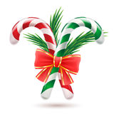 Candy canes with christmas tree branches and bow. Royalty Free Stock Photography
