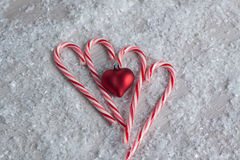 Candy Canes with a Heart Ornament. Candy canes in the shape of a heart surrounded by snow and a red heart ornament Stock Image