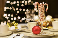 Candy canes and ornaments. On table with Christmas tree lights in background Stock Images