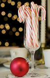 Candy canes and ornaments. On table with Christmas tree lights in background Royalty Free Stock Photography