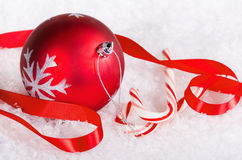 Candy canes with red Christmas ball Royalty Free Stock Photo