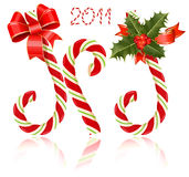 Candy canes with red ribbon and holly. Stock Images
