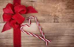 Candy canes and ribbon on wooden background Royalty Free Stock Photo