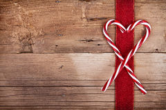 Candy canes and ribbon on wooden background Stock Photo