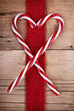 Candy canes and ribbon on wooden background Stock Photos