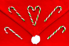 Candy Canes on Santa Hat as Christmas Background Stock Photo