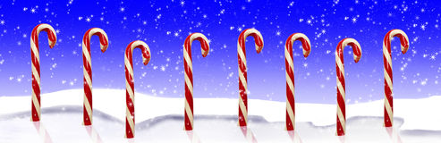 Candy Canes Snow. Red and white striped candy canes standing on frozen pond surface, drifts of snow and winter blue sky with snowflakes in background Stock Photo