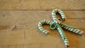 Candy canes tied in a bow on a wood background royalty free stock images