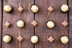 Candy in a chocolate wrapper and chocolate. Flat lay Stock Photos