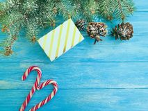 Candy, Christmas tree branch, festive decoration border present snow gift box on a blue wooden background present. Candy, Christmas tree branch, gift box a blue royalty free stock images