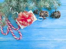Candy, Christmas tree branch, vintage festive decoration border present snow gift box on a blue wooden background present. Candy, Christmas tree branch, gift box royalty free stock photography