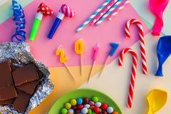 Candy, cioccolato, fischi, fiamme, palloni, 2017 candele sulla tavola di festa Immagini Stock Libere da Diritti