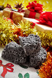 Candy coal and christmas gifts. Closeup of some lumps of candy coal and some christmas gifts in the background Royalty Free Stock Photos