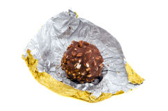Candy coated chocolate and nut  golden. Candy coated with chocolate and nuts rolled out of golden paper  on a white background Royalty Free Stock Images