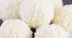 Candy in coconut flakes. Several white balls of sweets in dry coconut flakes stock video footage