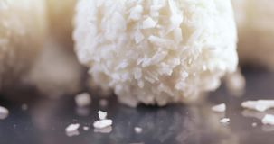 Candy in coconut flakes. Several white balls of sweets in dry coconut flakes stock footage