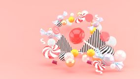 Candy among colorful balls on pink background stock images