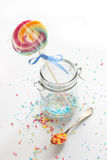 Candy - colorful sugar sprinkles and a lollipop. Colorful sugar sprinkles and a lollipop Stock Photography