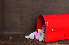 Candy conversation hearts spilling out of a red mailbox. For Valentine`s day stock photo