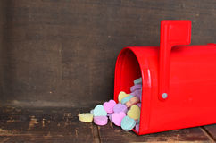 Candy conversation hearts spilling out of a red mailbox. For Valentine`s day royalty free stock photography