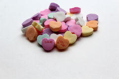 Candy Conversation Valentines Hearts. Pile of candy conversation hearts one saying Love the other saying You and Me. With copyspace for text stock photography